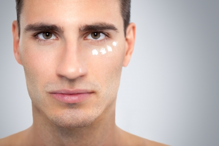 anti wrinkles: Face of handsome young man with moisturizer applied under his eyes.