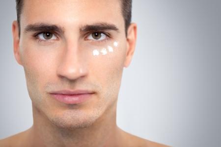 arrugas: Rostro de joven guapo con la crema hidratante aplicada bajo sus ojos. Foto de archivo