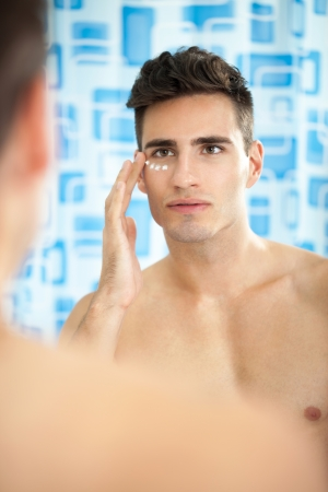 Handsome man applying cream on his face in bathroom  photo
