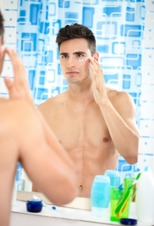 beautification:  young man applying moisturizer on his face front of mirror in bathroom Stock Photo