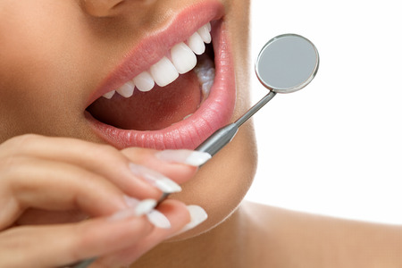 oral hygiene: Healthy smiling with great teeth and a dentist mirror Stock Photo