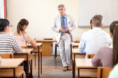 professor: Group of students study in classroom at high school with professor