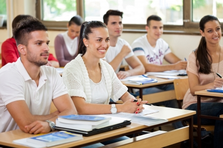young students in classroom listening a lecturer photo