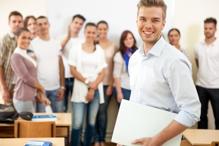 adult classroom:  Smiling young male student with colleagues in background