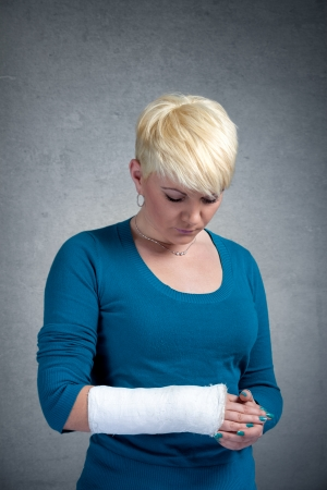 Sad woman looking at broken arm on her arm. photo