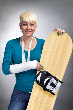 skiing accident:  Woman with broken arm holding snowboard and smiling