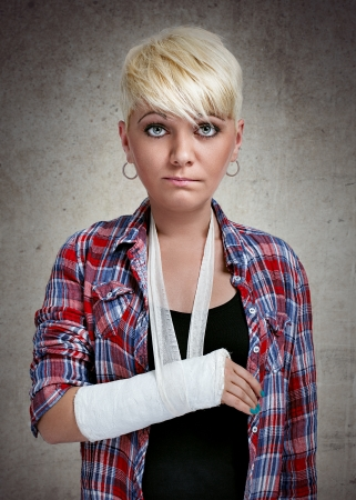 fracture arm:  funny sad girl with holding her painful  broken arm