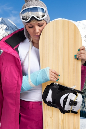 skiing accident:  sad woman with injured arm holding snowboard
