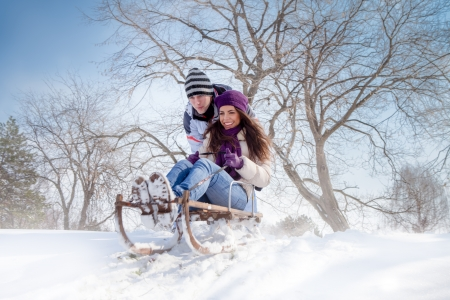 winter couple: young couple having fun with sleigh outdoor, winter season  Stock Photo