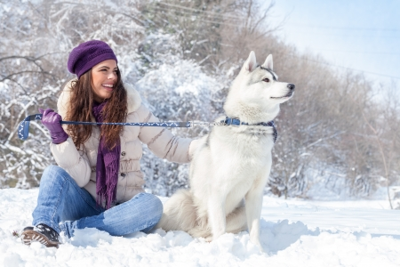 young beautiful woman sits with husky dog in the winter forest photo