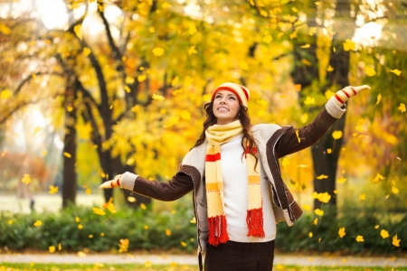 Portrait of a happy woman playing with autumn leaves in forest photo