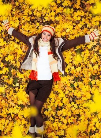 falling leaves: Young attractive woman lying on yellow leaves , top view