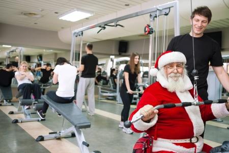 fitness hombres: Santa Claus haciendo ejercicios en un gimnasio Foto de archivo