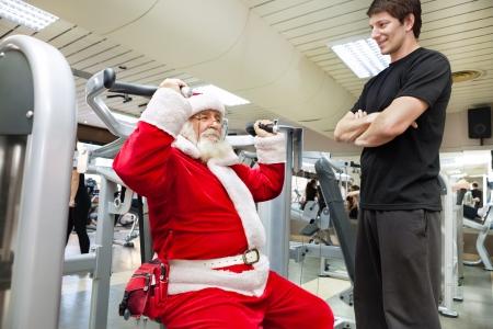 weihnachtsmann lustig: Weihnachtsmann Übung mit personal Trainer in der Turnhalle