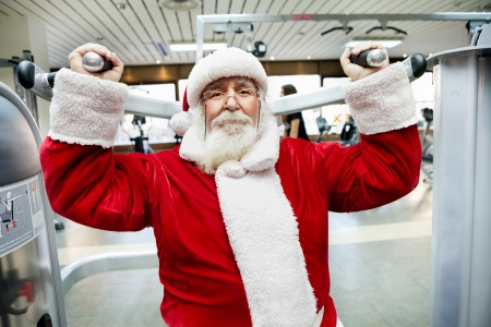 fitness club: Santa Claus  doing exercise on machine at gym