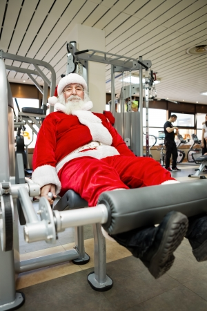 christmas funny: Father Christmas doing exercises before delivering presents Stock Photo