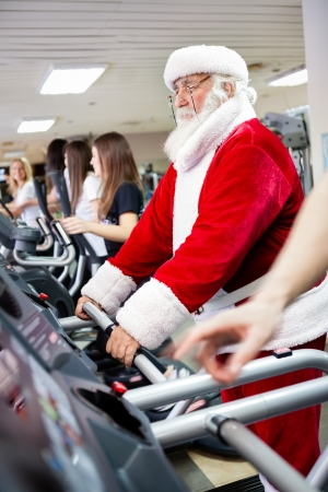 Santa Claus workout  on a treadmill at gym photo
