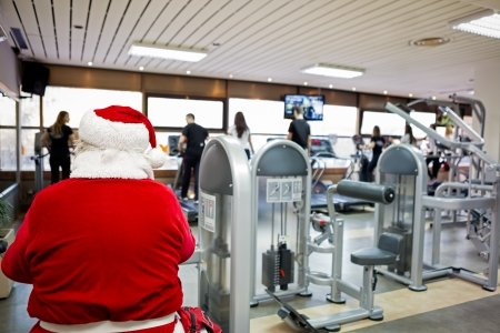Santa Claus at gym,  doing exercise and preparing for Christmas