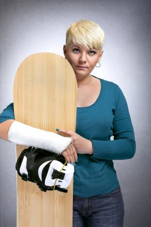 brazo roto: Chica Boarder con fractura de brazo que sostiene snowboard