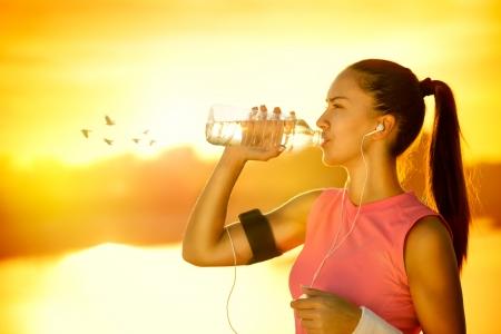 アスリート: スポーティな女性は晴れた日に屋外の水を飲む