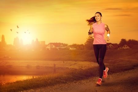 jog: Mujer atractiva joven que activa al aire libre en la puesta del sol Foto de archivo