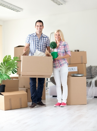Couple moving  home with lot of boxes around them photo