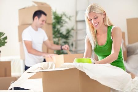 recien casados: pareja joven desembalaje moviendo cajas en una sala de estar