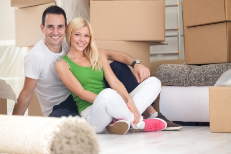 Adorable couple sitting on floor of their new home