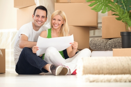family moving house: Young happy couple moving into their new home with plan