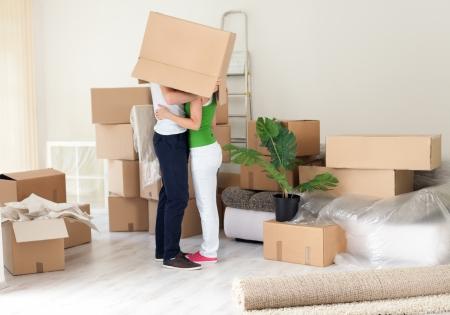 enamorados besandose: Pareja besándose con la caja en la cabeza en su nuevo hogar