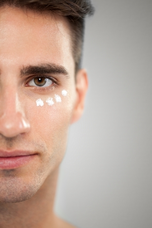 softness:  Portrait of man with cosmetic cream on skin around the eyes