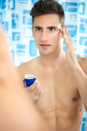 Young handsome man  with healthy skin applying cream photo