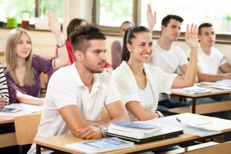 manos levantadas: Los estudiantes en el aula de contestar en la pregunta con las manos levantadas Foto de archivo