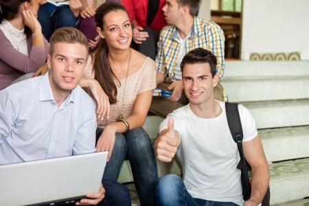 having a break: Students having fun during break with laptop school stairs Stock Photo