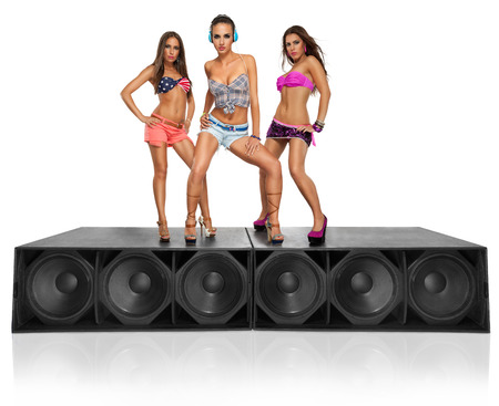 three seductive young girls standing on speakers photo