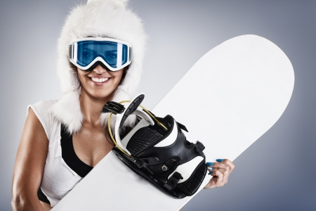 Beautiful young female snowboarder with white fur hat  photo