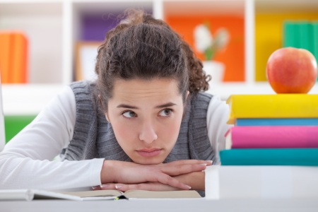 sad schoolgirl with learning difficulties with books