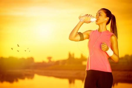 female jogger: corredora sed bebiendo agua de botella Foto de archivo