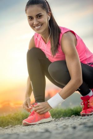 tying: smiling woman tying her sport shoe