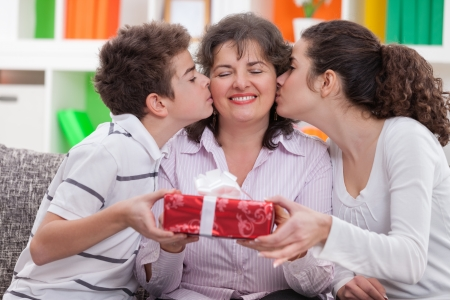 Happy mother receiving kisses from her children and smiling. Stock Photo