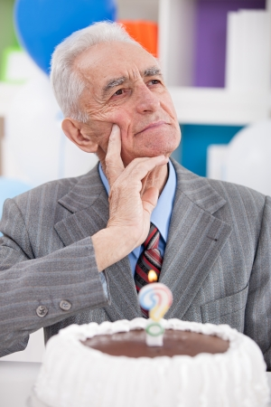 senior man with birthday cake thinking how old is photo