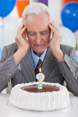 Senior man looking at  birthday cake thoughts about his age photo