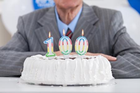 pastel de cumplea�os: torta de cumplea�os con velas encendidas durante un siglo, uno cent�simo cumplea�os Foto de archivo