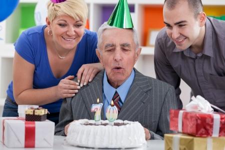 velas de cumpleaños: niños con el padre junto sopla en las velas en la torta de cumpleaños