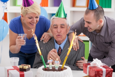 70 year old man: Senior man blowing candles with family and friends Stock Photo