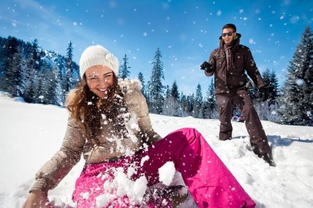 Jong paar spelen in de sneeuw, met sneeuwballengevecht Stockfoto