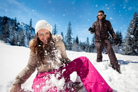 Young couple playing in snow, having snowball fight Фото со стока