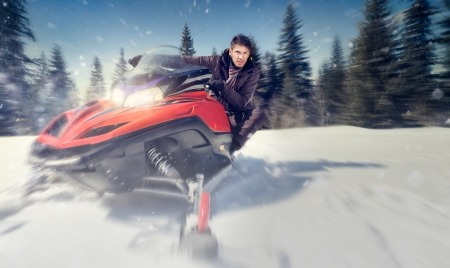 snowmobile:  young man driving  snowmobile at beautiful winter day - in motion