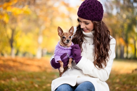 Cute woman with her Miniature Pinscher in autumn forest photo