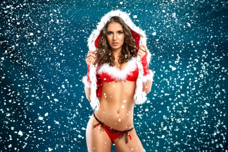 Young attractive sexy Santa, over snowy background photo